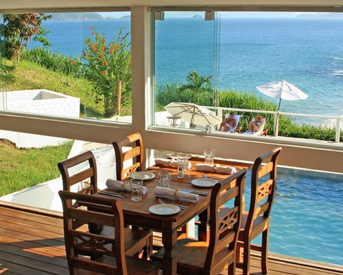 A well furnished dining area with a beach view.