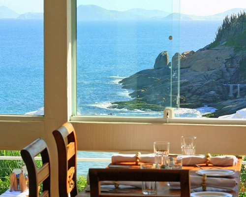 A well furnished indoor fine dining restaurant with an ocean view.