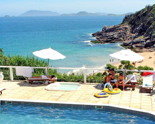 An outdoor swimming pool with hot tub chaise lounge chairs and thatched sunshades alongside the ocean.