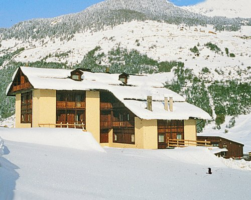 A street view of the Residenza Parco Dello Stelvio resort covered in snow.
