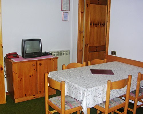 A well furnished dining area with a television.
