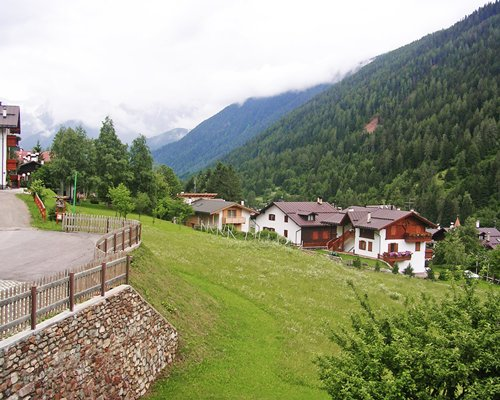 Scenic exterior view of units at Residenza Parco Dello Stelvio surrounded by wooded area.