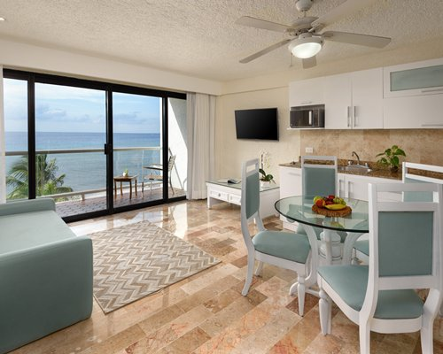 A well equipped kitchen with a glass top dining area and television alongside bedroom.