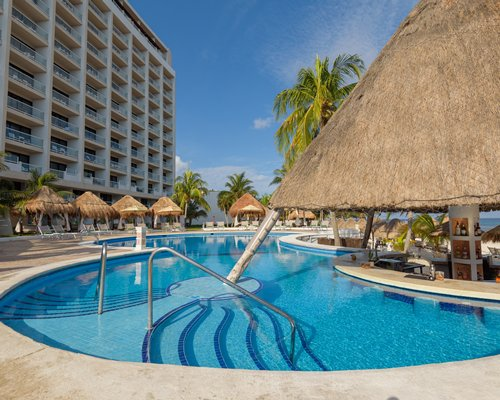 A lady having a cocktail in a bathtub with an ocean view at dusk.