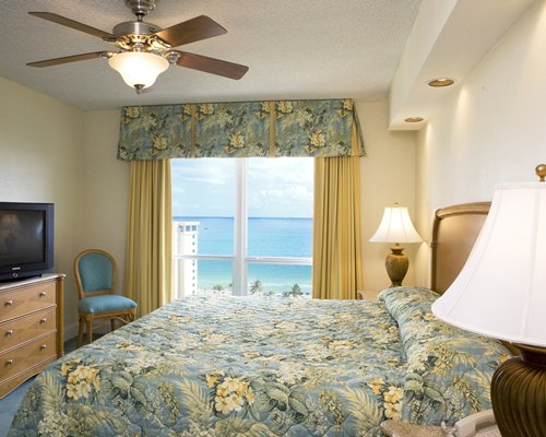 A well furnished bedroom with a television and beach view.