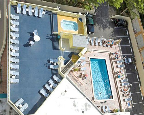 An aerial view of an outdoor swimming pool with a hot tub and chaise lounge chairs.