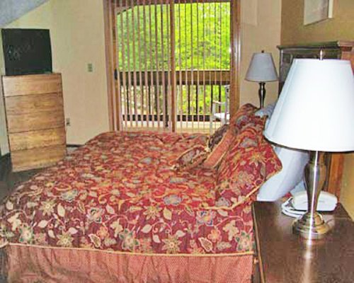 A well furnished bedroom with king bed television and balcony.