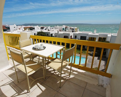 A balcony view with patio furniture alongside the ocean.
