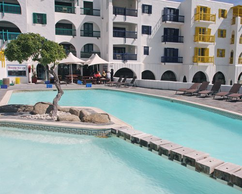 Outdoor swimming pool with chaise lounge chairs and sunshades alongside multiple unit balconies.