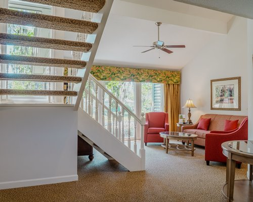 A well furnished living room with a queen pull out sofa alongside a staircase.