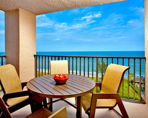 Balcony with patio furniture and beach view.