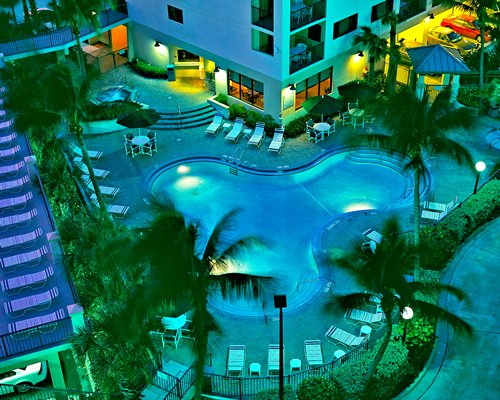 An outdoor swimming pool with chaise lounge chairs alongside resort units in neon lights.