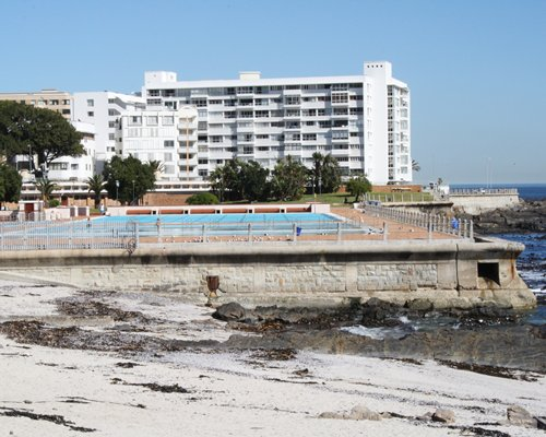 An outdoor swimming pool alongside the resort and the seashore.