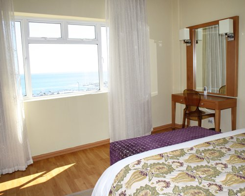 A well furnished bedroom with a mirror and beach view.