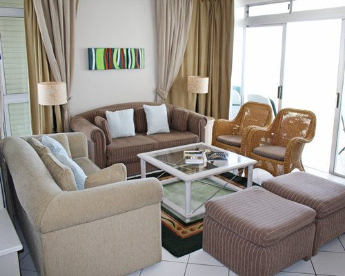 A well furnished living room with double pull out sofa and glass top teapoy.