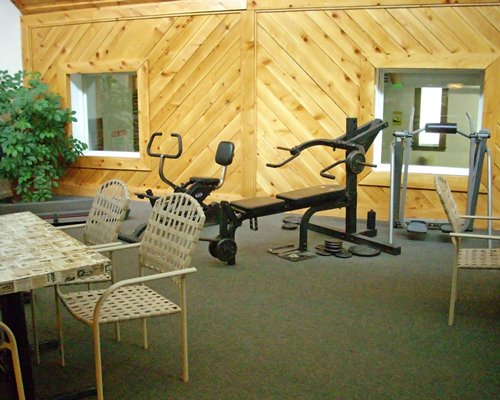 A well equipped fitness center with patio furniture.