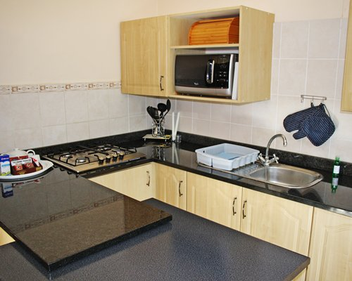 A well equipped kitchen with stove and microwave.