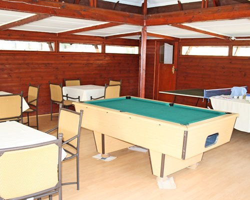 An indoor recreational room with a pool table and ping pong.