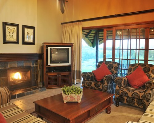 A well furnished living room with a fire in a fireplace and television.