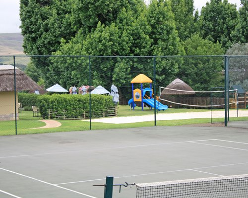 An exterior view of tennis and volleyball courts alongside kids playscape surrounded by wooded area.
