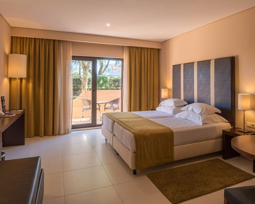 A well furnished bedroom with television and balcony.