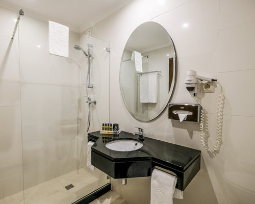 A bathroom with a stand up shower and a single sink vanity.