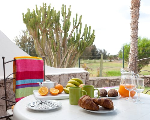 A view of croissant and fruits on the outdoor dining table.