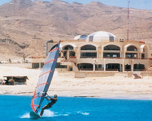 A man windsurfing on the water alongside the resort units.