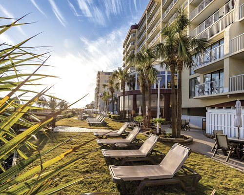 Scenic exterior view of the multi story resort units with chaise lounge chairs and palm trees.