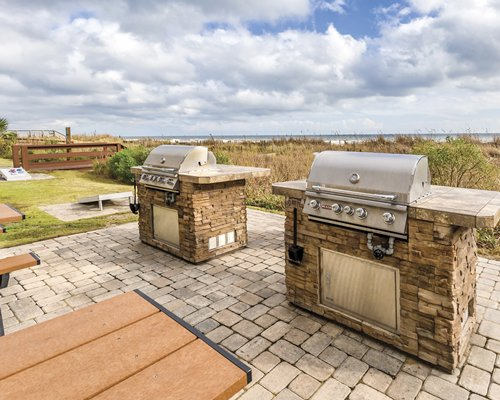 An outdoor two barbecue grills.
