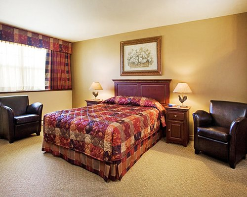 A well furnished bedroom with queen bed and an outside view.