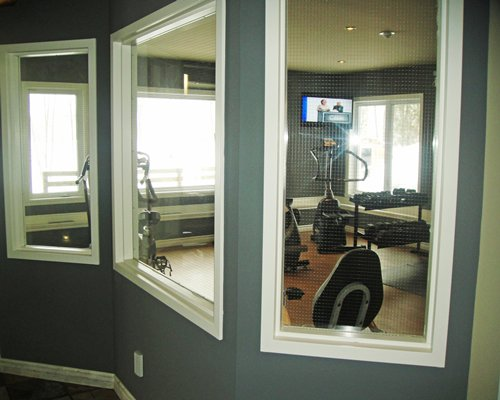 A well equipped indoor fitness center with an outside view.