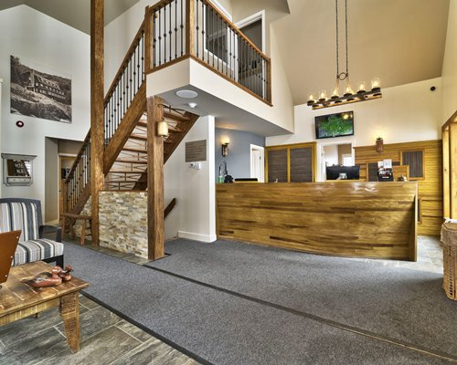 A well furnished reception area with a staircase and indoor balcony.