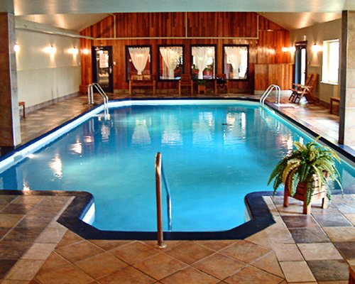 An indoor swimming pool alongside a well furnished area.