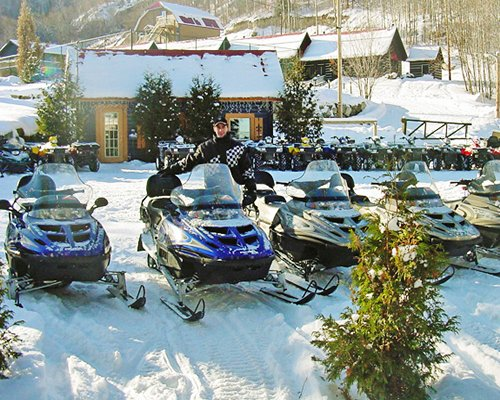 View of snowmobiles and the resort covered in snow.