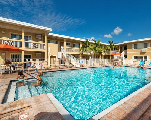 Outdoor swimming pool and chaise lounge chairs with view of multiple unit balconies.