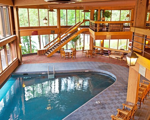 Indoor swimming pool with dining area wooden stairway balcony and outside view.