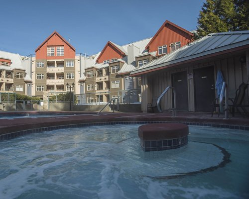 An outdoor hot tub with chaise lounge chair alongside multi story resort units.