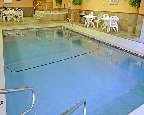 An indoor swimming pool with hot tub and patio furniture.