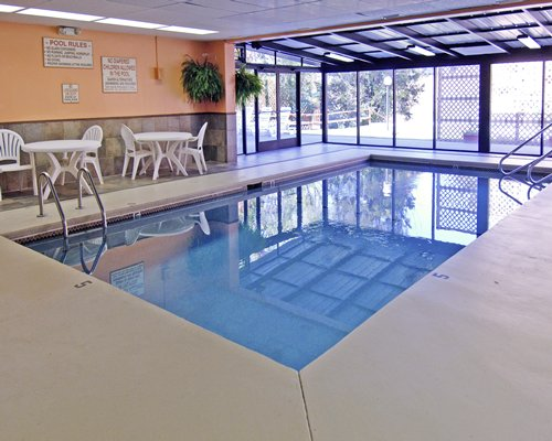 An indoor swimming pool with patio furniture and outside view.