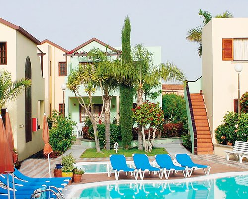 An exterior outdoor swimming pool with chaise lounge chairs alongside resort units.