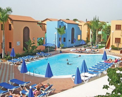 An outdoor swimming pool with chaise lounge chairs alongside the resort units.