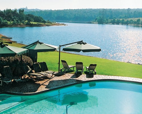 An outdoor swimming pool with chaise lounge chairs and landscaping alongside the lake.