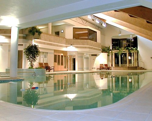 A large indoor swimming pool alongside a well furnished area.