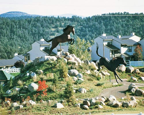 Horse statues at the entrance of Champions' Run Condominiums surrounded by wooded area.