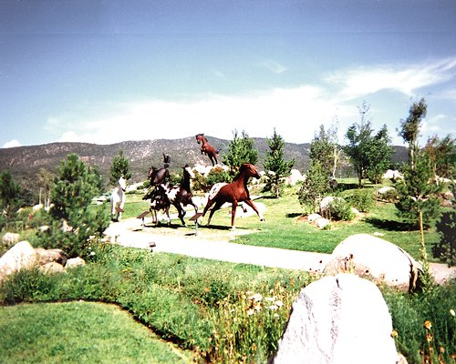 An exterior view of horse statues with trees and shrubs.