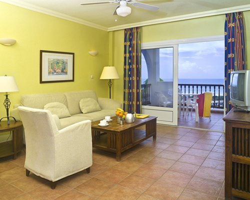 A well furnished living room with a television balcony patio furniture and beach view.