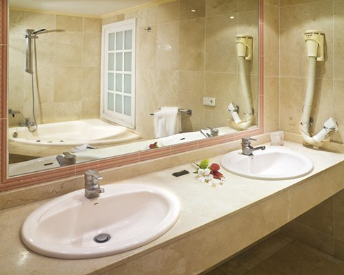 A bathroom with double sink bathtub and a shower stall.