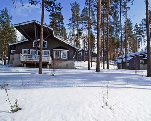 Exterior view of the units at Holiday Club Punkaharju surrounded by wooded area during winter.