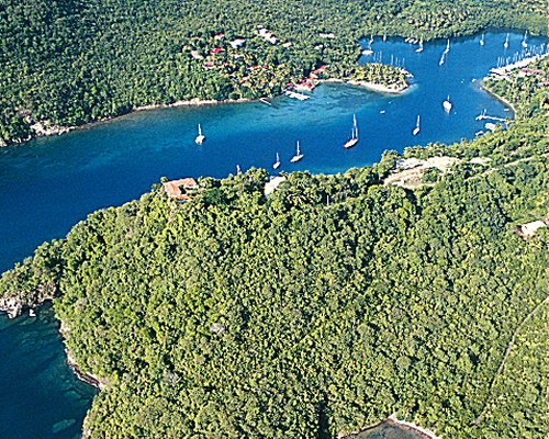An aerial view of boats sailing in a meander surrounded by wooded area.